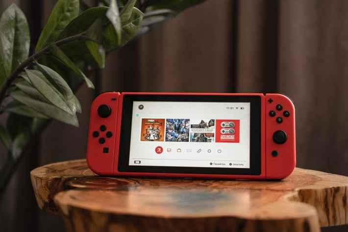 赤いニンテンドースイッチがテーブルモード状態でホーム画面を開いている画像